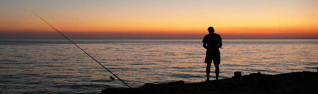 Angler am Meer im Abendlicht