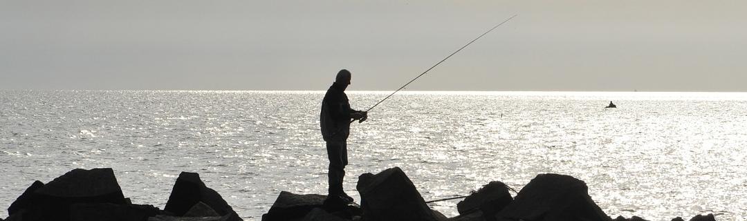 Angler auf Klippen am Meer im Abendlicht