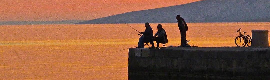 3 Angler auf einer Mauer im Abendlicht