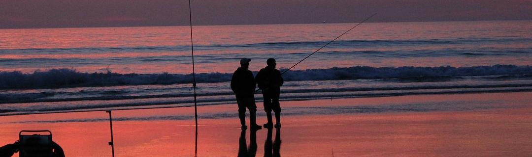 2 Angler am Strand im Abendlicht